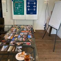 Visual van tafel die klaar is gemaakt voor teamcoaching met kaarten en flyers plus appeltaart